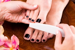 Pedicurist master makes pedicure on woman's legs - Spa treatment concept